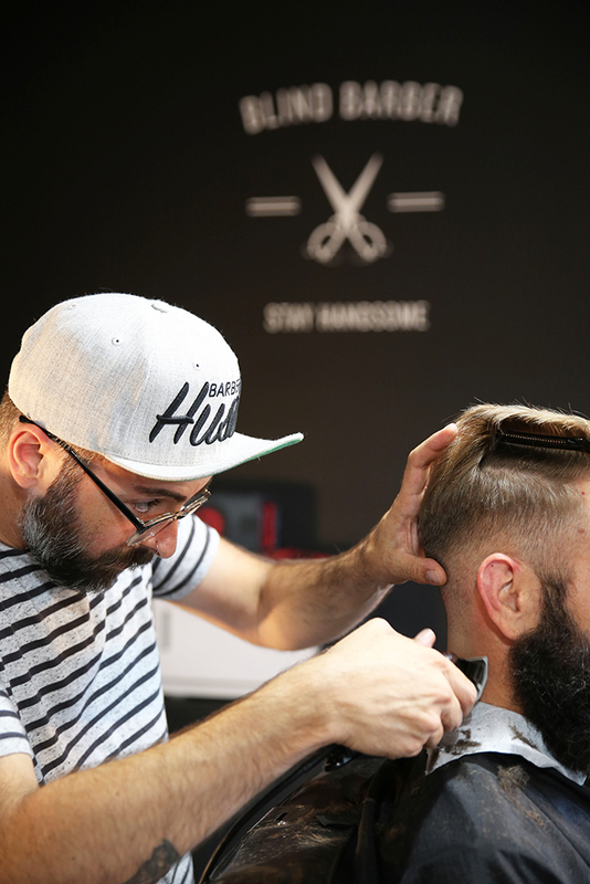 Photo of a man with a beard getting a haircut