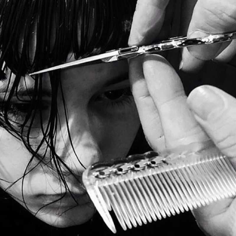 black and white up close photo of hair being cut with shears and comb in the frame