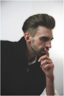 photo of a man with his hand on his chin with a rockabilly haircut