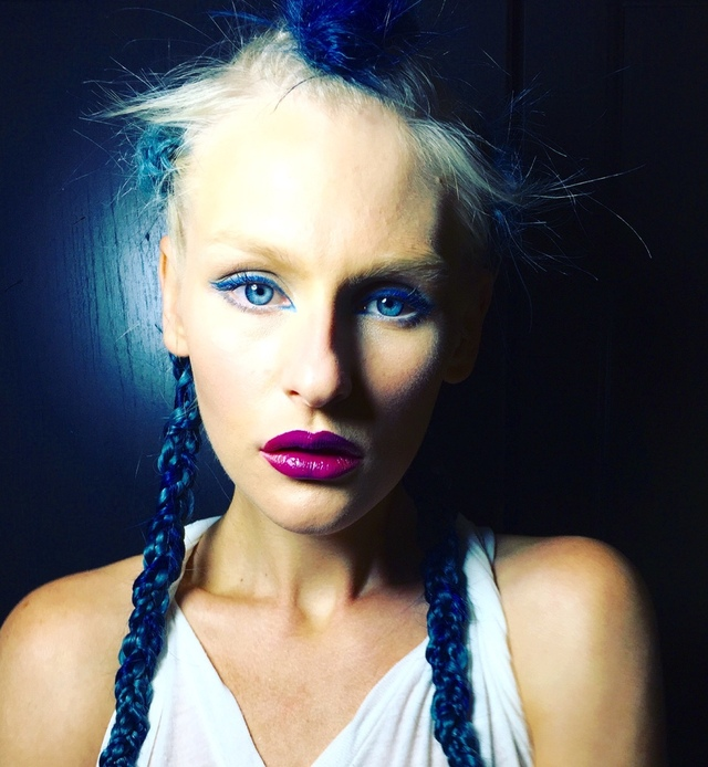 Photo of a model with blue hair weaved into her braids